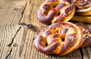 Pretzels, traditional German baked bread on rustic wooden table with free text space